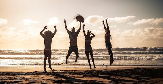 幸せな人々はビーチで夏休みの間に喜びと幸せでジャンプします