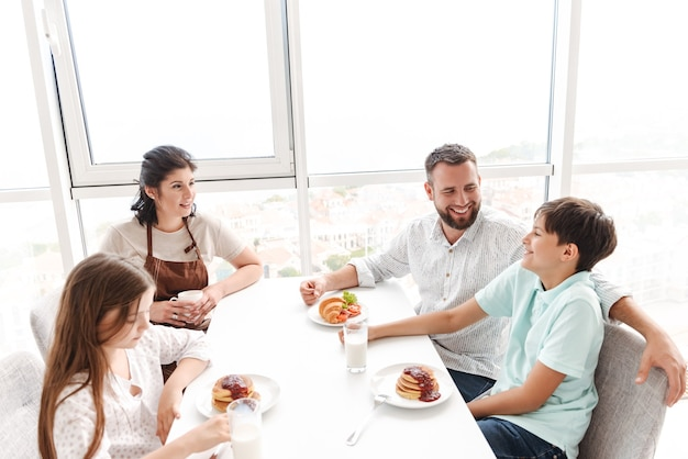 Счастливые люди родители с детьми 8-10 вместе завтракают на светлой кухне дома, едят круассаны и блины