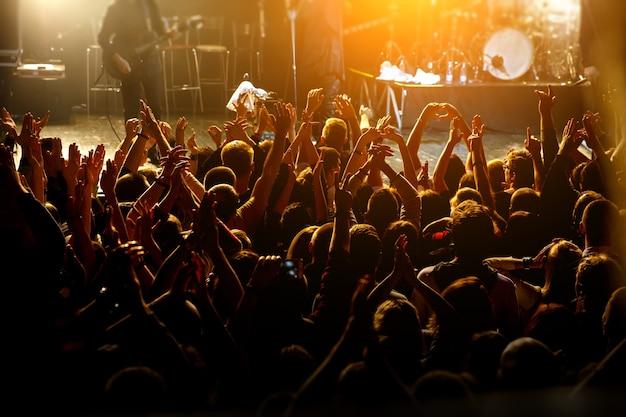록 콘서트에 손을 올리는 행복 한 사람들