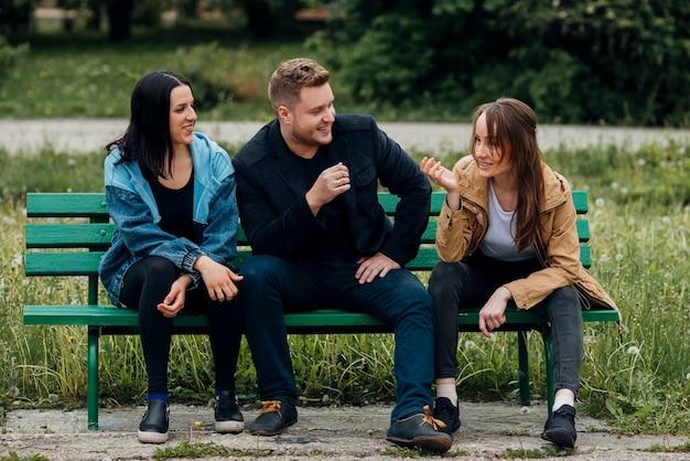 Счастливые люди отдыхают на скамейке и разговаривают