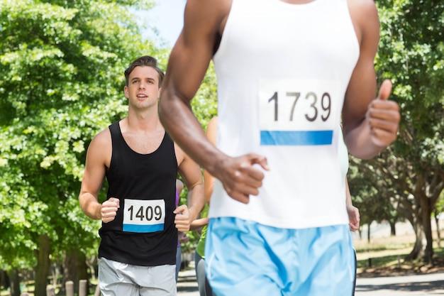 Счастливые люди бегут гонки в парке