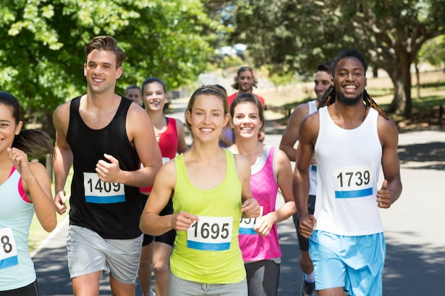 Happy people running race in park