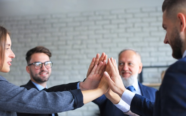 Happy people sitting in office and giving high five to their colleagues.