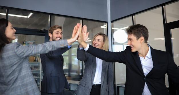 Happy people standing in office and giving high five to their colleagues.
