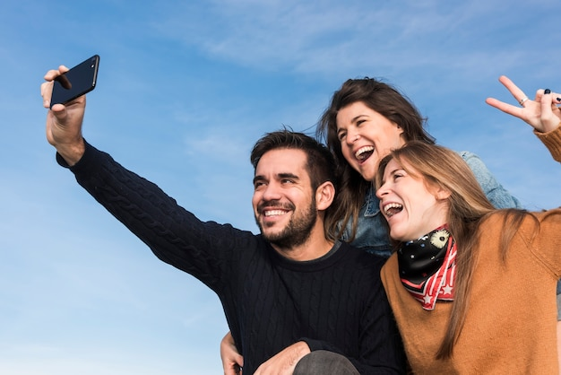 Happy people taking selfie on blue sky background