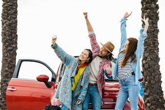 Happy people taking selfie near red car in street