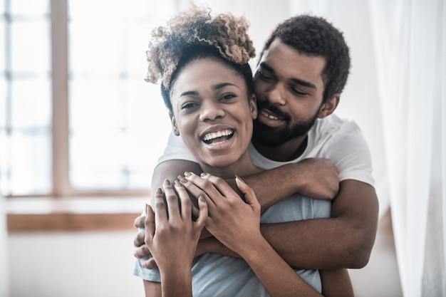 Счастливые люди. молодой взрослый темнокожий любящий мужчина обнимает радуясь смеющейся красивой женщине за плечи дома