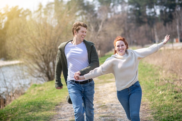 幸せな人々。晴れた日に自然の中で手をつないで長い生姜髪と気配りのある男性を持つ若い大人の熱狂的なランニング女性