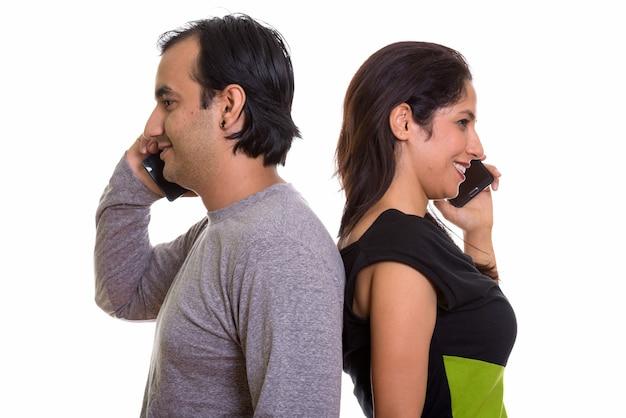 Счастливая персидская пара улыбается во время разговора по мобильному телефону
