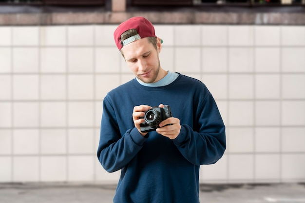 A happy person holding a vintage old camera and making photos