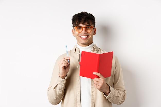 일기를 쓰고, 펜과 일기를 들고, 웃고, 흰 벽에 플래너와 함께 서있는 일정을 계획하는 안경에 행복한 사람.