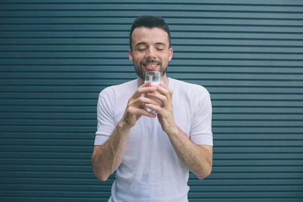 Счастливый человек стоит и держит стакан молока. он держит глаза закрытыми и наслаждается моментом. изолированные на полосатый