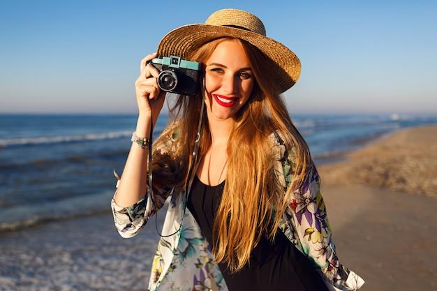 Счастливая мелкая женщина с длинными светлыми волосами веселится и фотографирует на пляже у океана на старинную камеру, солнечные цвета