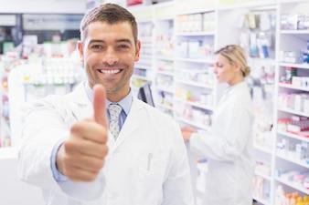 Happy pharmacist holding his thumb