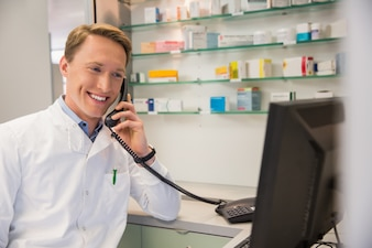 Happy pharmacist on the phone using computer