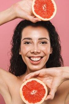 ピンクの背景で隔離の長い髪の笑顔とグレープフルーツの断片を保持している半分裸の女性の幸せな写真