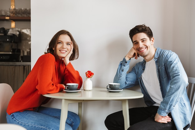 Happy photo of young woman and man smiling and looking at you, while sitting at table in restaurant