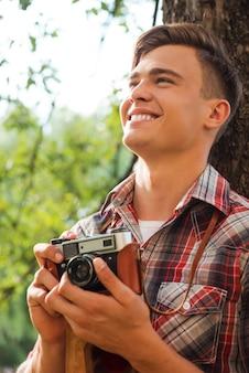 幸せな写真家。ヴィンテージカメラを持って、木に寄りかかって笑っているハンサムな若い男