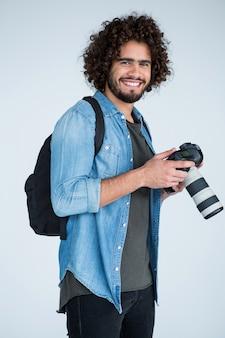 Счастливый фотограф с фотоаппаратом в студии