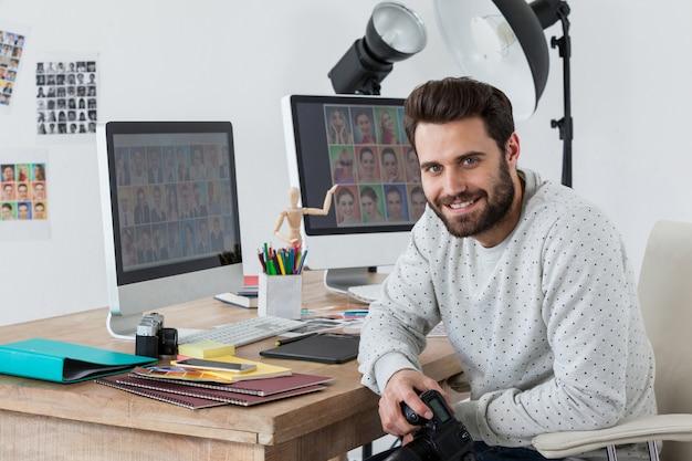 그의 책상에서 카메라를 들고 행복 한 사진 작가