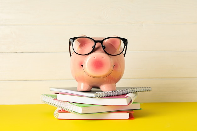 Happy piggy bank with glasses, and copybooks on color table against white wooden background
