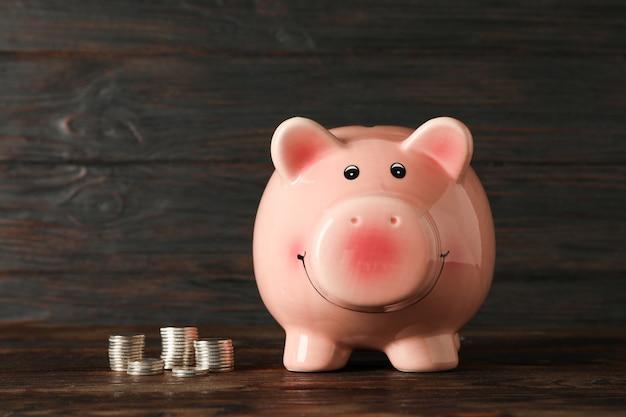 Счастливая копилка с деньгами на деревянный стол на деревянном фоне