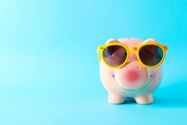 Happy piggy bank with sunglasses on color background