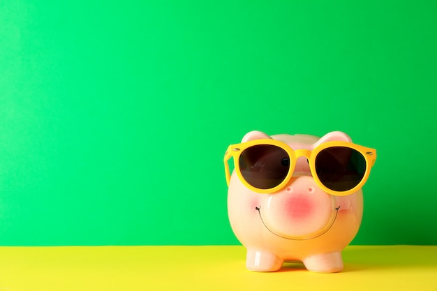 Happy piggy bank with sunglasses on color table against green background