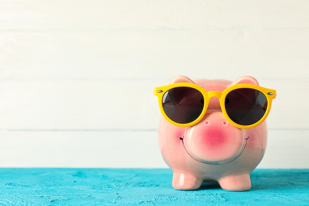 Happy piggy bank with sunglasses on color table against white wooden background