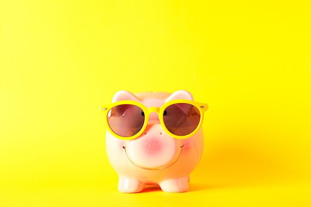 Happy piggy bank with sunglasses on yellow background