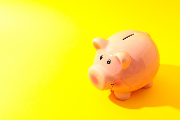 Happy piggy bank on yellow background