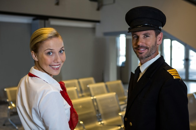 Happy pilot and air hostess standing in the airport terminal