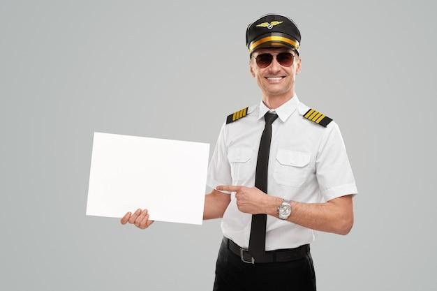 白紙の白い紙を示す幸せなパイロットの男