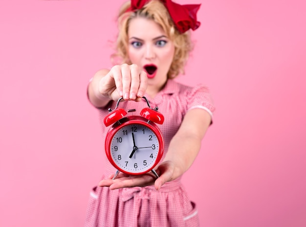 Happy pin-up woman holding clock. surprised pin up woman in red dress holds red clock. pin up style lady. retro style. saving time concept. summer sale. discount. isolated on pink background.