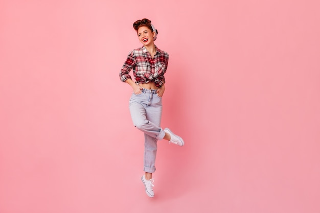 Happy pinup girl posing with hands in pockets. laughing ginger woman in checkered shirt standing on pink space.
