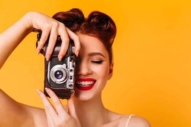 写真を撮る幸せなピンナップガール。黄色の空間に分離されたカメラを持つ女性のスタジオポートレート。