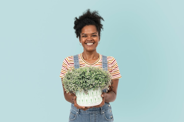 Happy plant parent holding potted shrubs