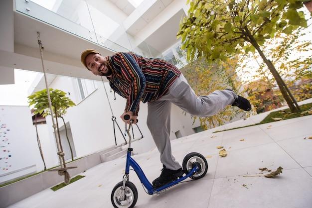 彼の現代的な家の前でスクーターに幸せな遊び心のある大人