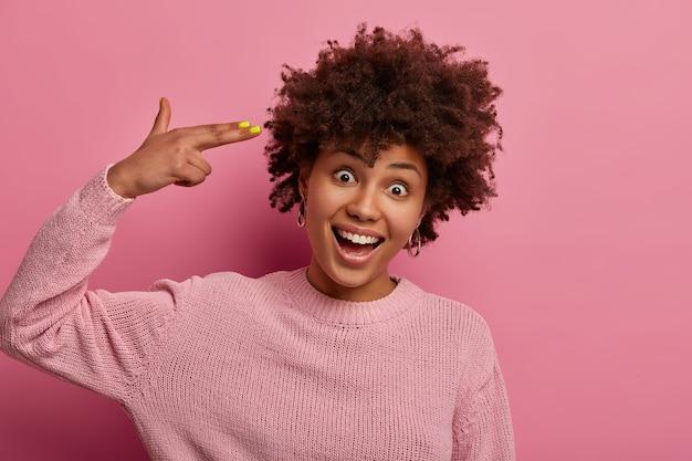 행복한 쾌활한 아프리카 계 미국인 여자는 손가락 총 권총을 만들고, 긍정적으로 웃고, 머리를 기울이고, 장밋빛 점퍼를 착용하고, 긍정적 인 분위기를 가지고 있으며, 광범위하게 미소를 지으며 분홍색 벽에 고립되어 있습니다. 신체 언어 개념