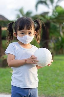 Счастливая шаловливая азиатская девушка ребенка нося тканевую маску. она играет в мяч на детской площадке в зеленом парке.