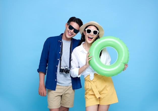Счастливый игривый азиатский турист пара, одетый в летнюю одежду и пляжные аксессуары, чтобы поехать в отпуск на синем.
