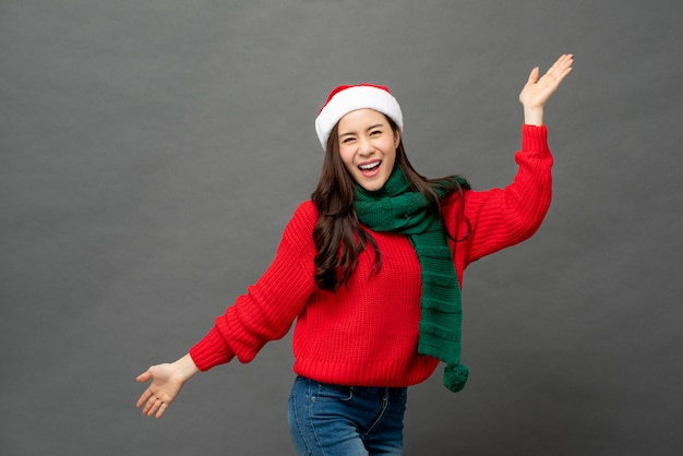 Happy playful asian woman in red and green christmas attire