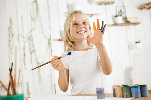 Happy and playful cute freckled blonde girl dressed in white, holding brush in one hand and showing another hand, which she messed up with paint.