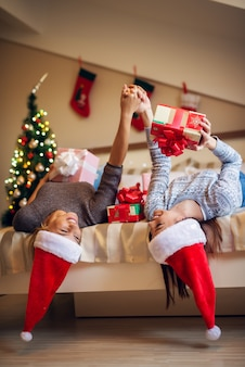Счастливые игривые милые рождественские друзья с санта шляпы и свитера, наслаждаясь дома на праздники.