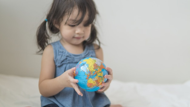Happy playful toddler looking at globe ball on bed in bedroom at home.