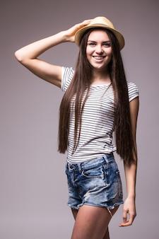 肩越しに横を向いている夏のわらのフェドーラ帽を身に着けている幸せな遊び心のある女性
