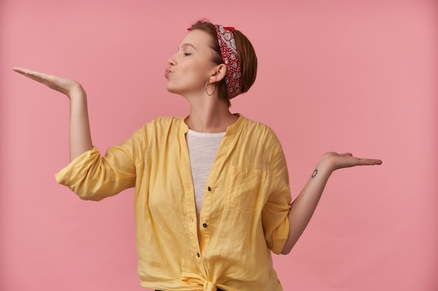 Happy playful young woman in yellow shirt with headband on head holding empty space on both palms and sending a kiss over pink wall