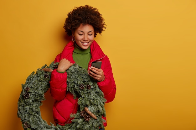 Happy pleasant looking curly haired woman uses mobile phone for chatting online, carries handmade wreath