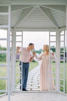 사랑에 빠진 행복한 성숙한 부부는 야외 나무 전망대에서 함께 서서 라벤더 향기를 즐깁니다. 로맨틱 데이트, 결혼 기념일 축하
