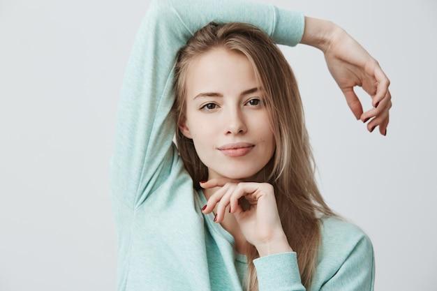 Счастливая довольная блондинка европейской внешности с темными глазами в синем топе с длинными рукавами смотрит и улыбается